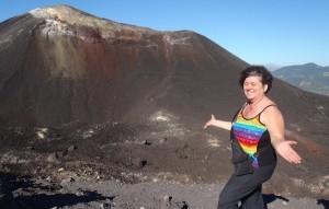 Eva van Loon in a rainbow striped top standing on top of a volcano in Nicaragua.